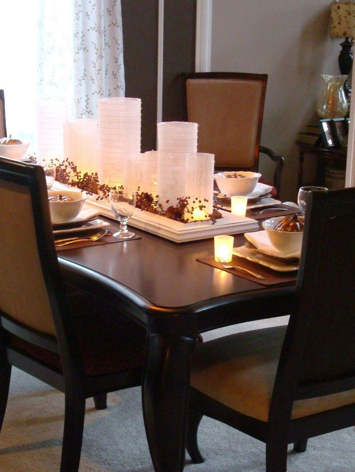White lanterns lit up with candles add a shimmering touch to this breakfast table