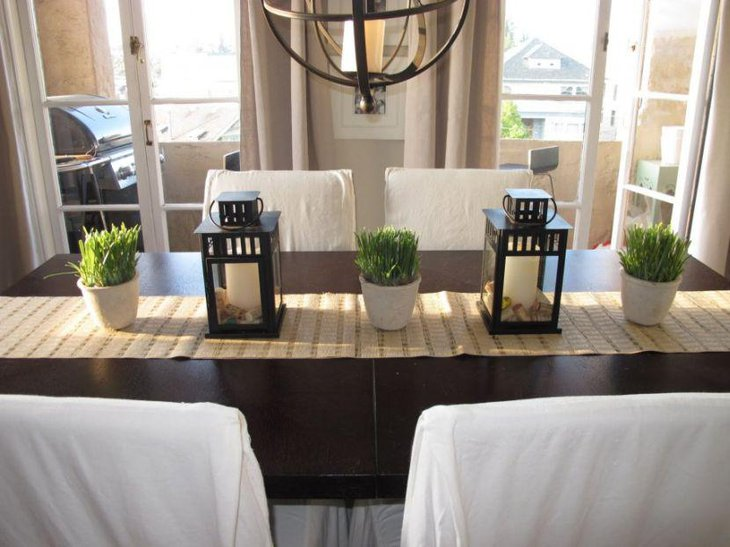 White pillar candle decor in black lanterns looks amazing
