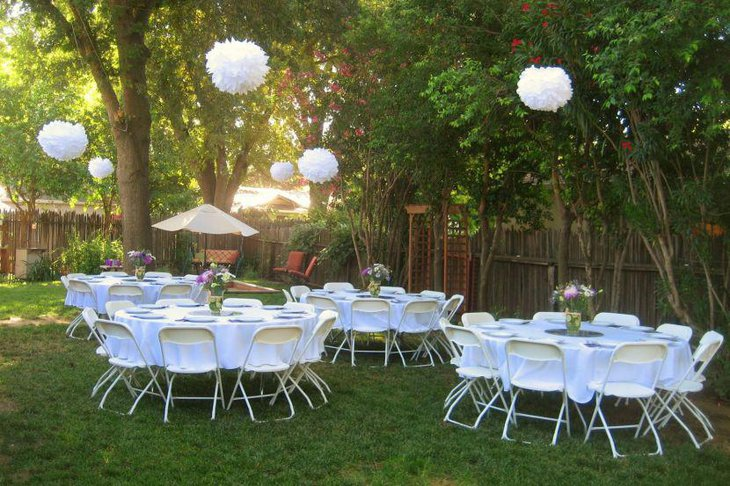 White themed bridal shower tables decorated with floral vases
