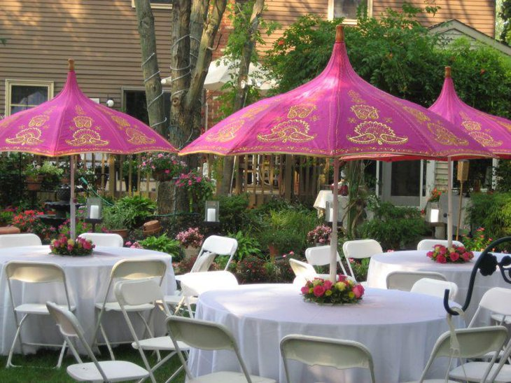 White wedding garden party table decor with flower bouquets and pink umbrellas as centerpieces