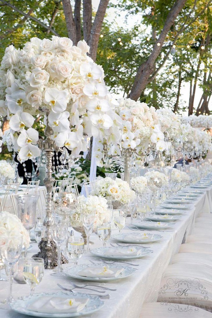 Winter wedding table decor with silver vases and white flower arrangements