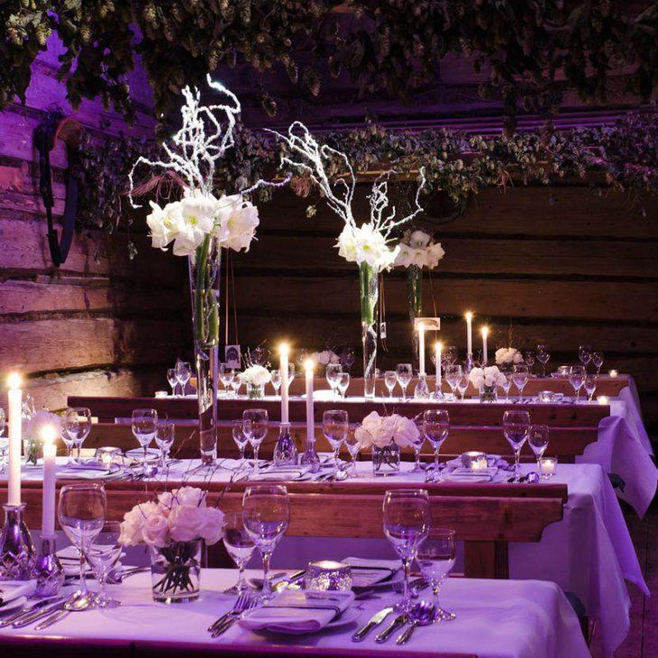 Winter wedding table setting with tall glass floral centerpiece