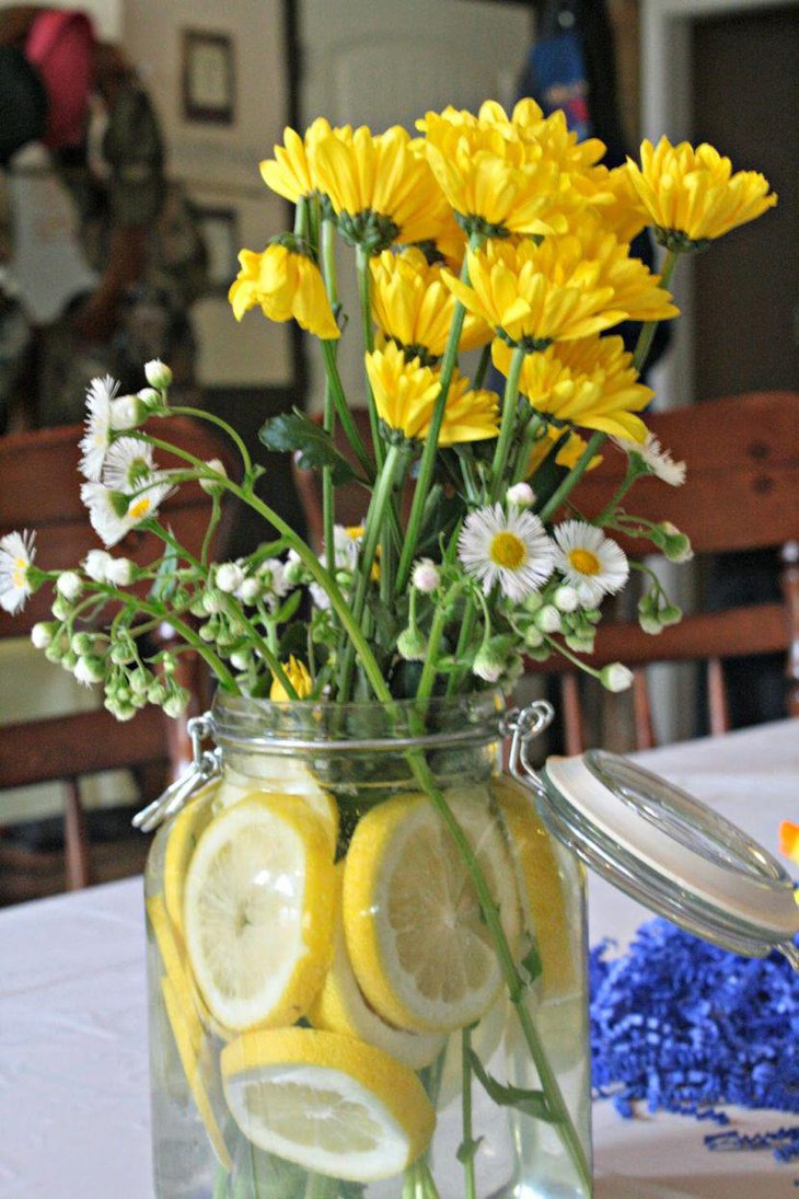Yellow flowers decorated in grey jar filled with lemon slices for a gorgeous look